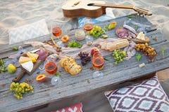Pique-niquez sur la plage au coucher du soleil dans le style de boho, nourriture et buvez concentré Photographie stock