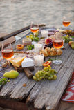 Pique-niquez sur la plage au coucher du soleil dans le style de boho, nourriture et buvez concentré Photo libre de droits