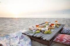 Pique-niquez sur la plage au coucher du soleil dans le style de boho, nourriture et buvez concentré Image libre de droits