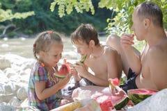 Piquenique da família do pai e das duas crianças com melancia suculenta foto de stock