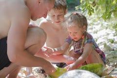 Piquenique da praia do verão do pai e dos dois irmãos fotografia de stock royalty free