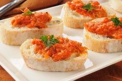 Piquillo och kronärtskockabruschetta på italienskt bröd royaltyfria bilder