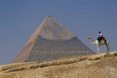 Pirámide de Khafre (Chephren) en Giza - El Cairo, Egipto con una policía turística en un camello Imagen de archivo libre de regalías
