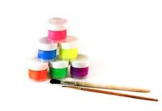 Pirámide de latas de pintura y de dos cepillos para pintar en un blanco Foto de archivo libre de regalías