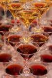 Pirámide de los vidrios para los colores de las bebidas, del vino, del champán, rojos y amarillos, celebración festiva del humor Imagenes de archivo