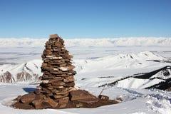 Pirámide de piedra en el top de la montaña, opinión sobre el lago Issyk Kul val Imagen de archivo libre de regalías