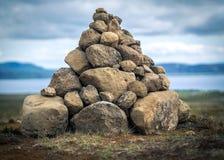 Pirámide de piedra en Islandia en un fondo del cielo y del lago Imagen de archivo libre de regalías