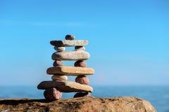 Pirámide de piedras en la costa imagen de archivo