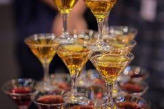 Pirámide de vidrios con las bebidas de oro y rojas, vid, vino, champán, humor festivo, celebración Imagenes de archivo