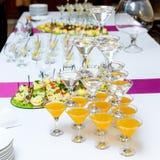 Pirámide de vidrios con las bebidas y del vino en la tabla de banquete Imagen de archivo