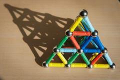 Pirámide del juguete del imán en el escritorio con la sombra Imágenes de archivo libres de regalías