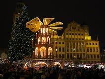 Pirâmide, árvore e povos do Natal no mercado na noite Fotos de Stock