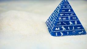 Pirâmide azul abstrata com o hieróglifo que fica na areia imagem de stock royalty free