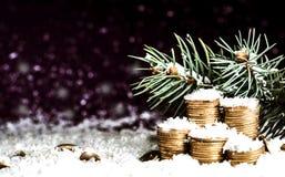 A pirâmide das moedas e das moedas dispersou sobre na neve Foto de Stock
