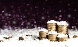 A pirâmide das moedas e das moedas dispersou sobre na neve Fotos de Stock