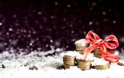 A pirâmide das moedas e das moedas dispersou sobre na neve Imagens de Stock