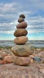 Pirâmide das pedras na praia, contra um céu azul com nuvens brancas foto de stock