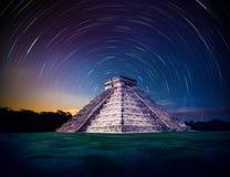 A pirâmide de El Castillo em Chichen Itza, Iucatão, México, na noite com estrela arrasta fotografia de stock