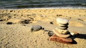 Pirâmide de pedra do zen em uma praia com ressaca video estoque