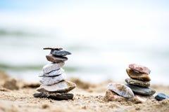 Pirâmides das pedras na areia Mar no fundo Imagem de Stock Royalty Free