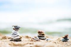 Pirâmides das pedras na areia Mar no fundo Imagens de Stock Royalty Free
