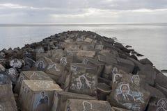 Pir de piedra abajo al mar con los bloques de cemento pintados Foto de archivo libre de regalías