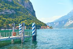 Pir eller kajen för skepp och fartyg på branta alpina banker av den härliga sjön Como med parkerade fartyg och yachter near byn Arkivfoto