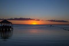 Pir, fartyg och havet och solnedgången Arkivbild