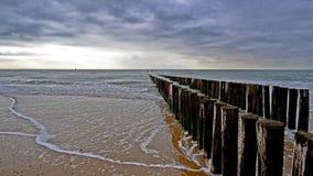 Pir och saktar vågor under molnigt väder på stranden i Zeeland i Nederländerna Arkivfoto
