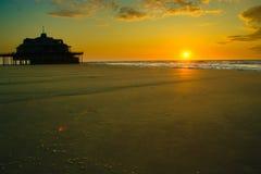 Pir vid lågvatten under solnedgång royaltyfri bild