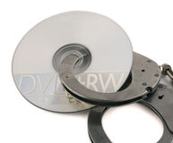 Piracy. A pair of handcuffs and a dvd royalty free stock photography