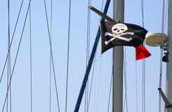 Piracy flag. A black piracy flag with a skull and bones on a mast Stock Photos