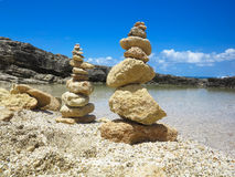 Piramide堆禅宗在海和蓝天附近扔石头 免版税图库摄影