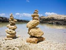 Piramide堆禅宗在海和蓝天附近扔石头 免版税库存照片