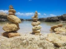 Piramide堆禅宗在海和蓝天附近扔石头 免版税库存图片