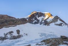 Piramide文森特在日落的峰顶和Gnifetti山小屋, Monte 免版税图库摄影
