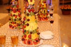 Piramide della frutta fresca e bacche su una tavola con vino rosso e champagne fotografie stock