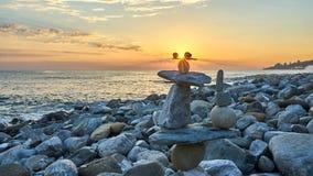 Piramide delle pietre isolate sul tramonto, fondo della spiaggia fotografia stock