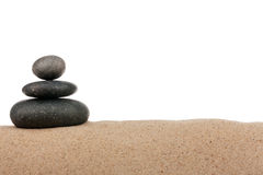 Piramide delle pietre nere sulla spiaggia di sabbia Isolato su una priorità bassa bianca Immagini Stock Libere da Diritti