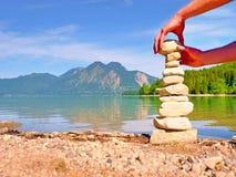 Piramide delle pietre piane su una spiaggia ciottolosa del lago, montagne all'orizzonte fotografia stock libera da diritti