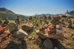 Piramide delle pietre su un fondo delle montagne Fotografia Stock