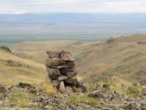 Piramide delle pietre su un fondo delle montagne Fotografie Stock