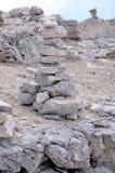 Piramide delle pietre sulla stabilità del fianco di una montagna immagini stock