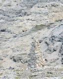 Piramide delle pietre sulla stabilità del fianco di una montagna fotografie stock