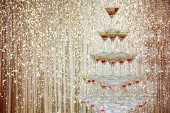 Piramide scintillante del champagne, torre dei vetri al partito davanti alla parete dorata Fotografie Stock Libere da Diritti