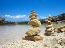 Piramide stack of zen stones near sea and blue sky Stock Images