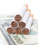 Piramide van sigaretten die op geld leggen Stock Foto's