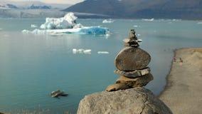 Piramide van stenen tegen de achtergrond van de Gletsjerlagune van Jökulsà ¡ rlà ³ n royalty-vrije stock afbeelding