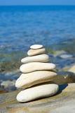 Piramide van stenen zen saldo in overzeese kust Royalty-vrije Stock Afbeeldingen