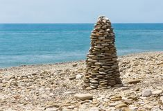 Piramidekiezelsteen op overzees strand Stock Afbeeldingen
